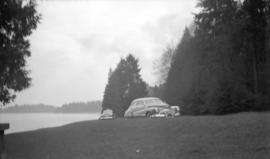 [Cars driving along waterfront at Stanley park passing Chaythoos, the site where Lord Stanley ded...