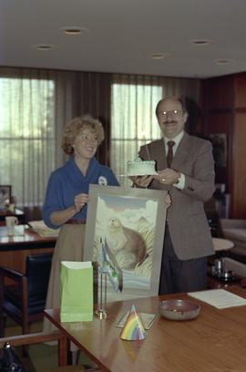Mike Harcourt holding a cake with Centennial staff member holding an otter poster
