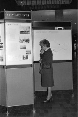 Woman viewing the Vancouver City Archives' display, Portholes and Pilings