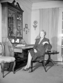 [Woman seated at writing desk in a living room]