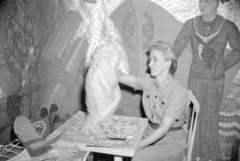[Sculptor at work in elaborately decorated studio]
