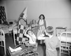 [Woman from the Junior League dressed up in a clown mask and costume entertaining hospitalized ch...