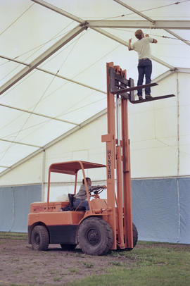 Man operating forklift inside event tent