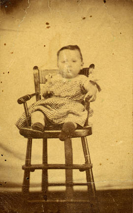 [Studio portrait of a baby in a high chair]