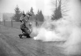 [Member of the C.O.T.C. setting off smoke bombs as part of a mock battle]