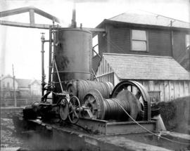 [Steam donkey engine next to buildings]
