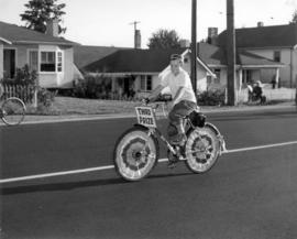 "[A boy riding a bike with a sign ""Third Prize"" during a parade in Kerrisdale]"