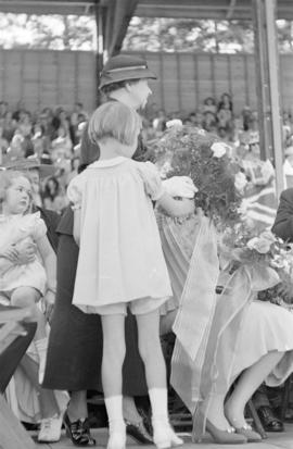Woman and child holding flowers at Golden Jubilee opening ceremonies at Brockton Point Grandstand