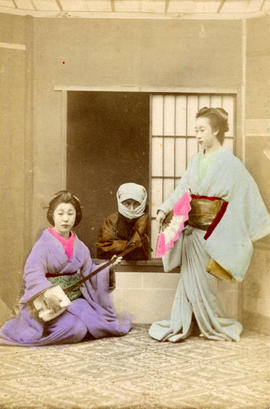 [Studio portrait of two women and a man in formal Japanese dress]