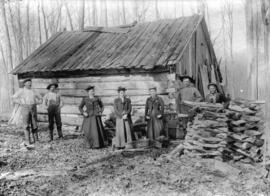 [Three women and four men assembled in front of partially constructed log cabin]