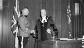 [Portrait of Mayor Cornett and Captain Larson of the St. Roch shaking hands in the Mayor's o...
