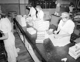[Woman packaging paper napkins for] Pacific Mills