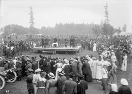 Men on a stage surrounded by a crowd in a park