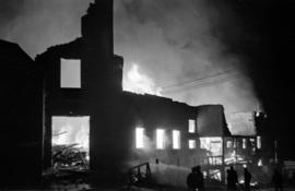 Silhouette of Denman Arena ablaze, with firefighters in foreground