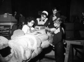 Three boys watch Kwakiutl carver Ellen Neel carving a totem pole