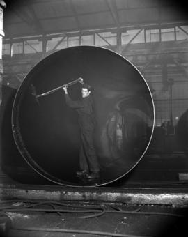 [Man painting or washing the interior of a boiler at Vancouver Iron Works Ltd.]