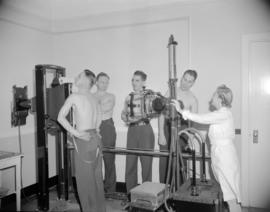 [Men lining up at an x-ray machine for tuberculosis screening]