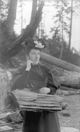 [Mrs. H.W. Maynard standing on beach near Brockton Point, Stanley Park]