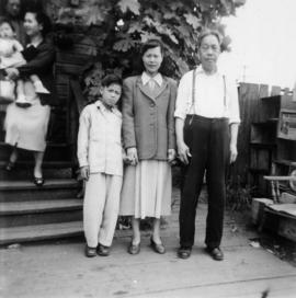 Gum May Yee, Guy Yee, and Foon Wong at the entrance to a house (women and child in background)