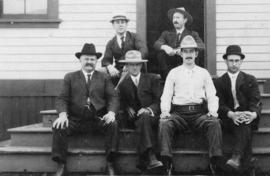 [Six men sitting on steps outside building]
