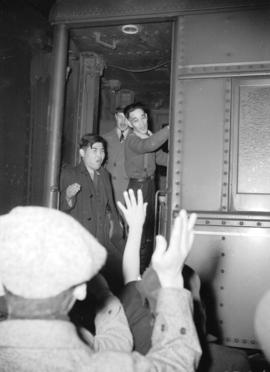 [Japanese evacuees entering train while friends and family wave from the train platform]