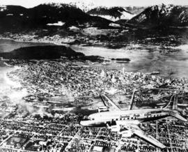 "[Oblique view of] ""Empress of Vancouver"" over city of Vancouver."