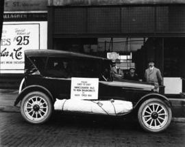 "[Car at Reo Motor Car Agency, loaded for trip with sign ""From coast to coast Vancouver B.C. ..."