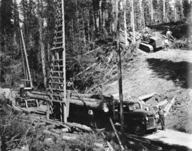 Upper Fraser Mills.  Loading logs on truck and small skidding tractor bringing in logs