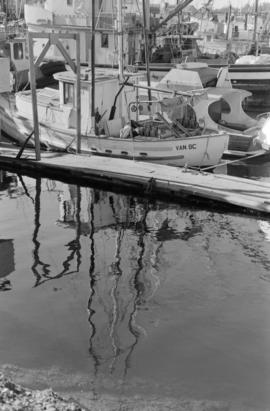 Two boats tied up to a dock with reflection in the water