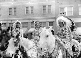 [Three Stoney Indians on horseback at the Calgary Stampede parade]
