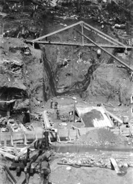 [Workers, scaffolding and machinery in excavated area for Buntzen Lake Power Plant number one]