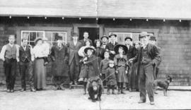 [Group photograph in front of the entrance to a home]