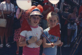 Two girls holding flags and balloons
