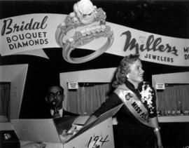 Miss P.N.E., Glenda Sjoberg, drawing ticket from box at Millers Jewelers display in Manufacturers...
