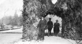 [Man and couple at the evergreen arch in Stanley Park]