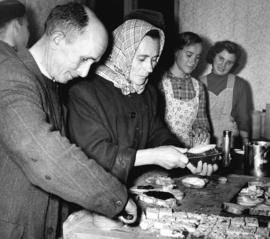 [Hungarian refugees help themselves to food in the Immigration Building at the airport]