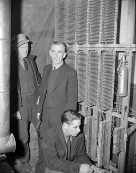 [Technicians working on equipment at the Mission Telephone Company]