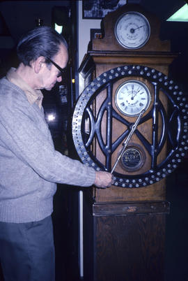 Elek Imredy and old time clock during Vancouver Historical Society tour of Grocery Hall of Fame