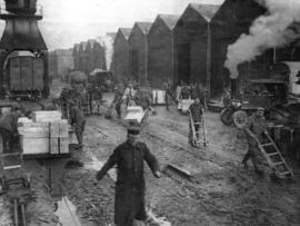 [Soldiers move goods for the Western Front on a quay lined with store houses]