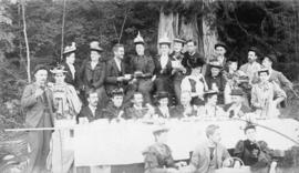 [Group of men and women eating strawberries at a picnic table]