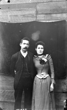 [Man and woman posing in front of sheet placed on exterior of building]
