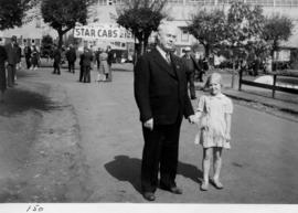 Mayor Lyle Telford and daughter on fairgrounds behind Grandstand