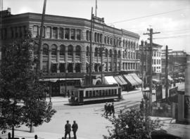 [View of buildings, streetcar, and pedestrians at Hastings and Cambie Streets]