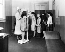 Girls being weighed by school nurse at Open Air School