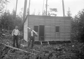 [Two men, one holding a gun and one holding a saw, standing in front of a partially completed hou...