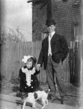 [Unidentified man standing in front of house with girl, age] 3 y[ea]rs, 3 mo[nths, and dog]