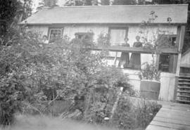 [Unidentified men and women in front of house]