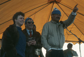 Mike Harcourt at microphone accompanied by two men on stage at Polar Bear Swim