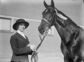 Woman holding horse with ribbons