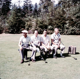 Group of men seated on golf course